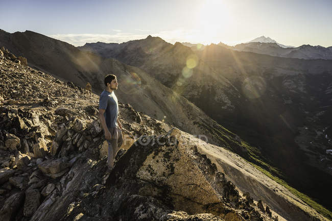 Male mountaineer looking out from top of mountain range, Nahuel Huapi National Park, Rio Negro, Argentina - foto de stock