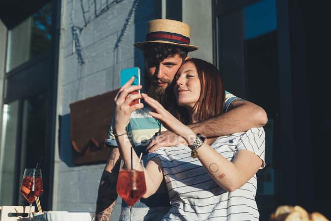 Casal tomando selfie smartphone no café calçada — Fotografia de Stock