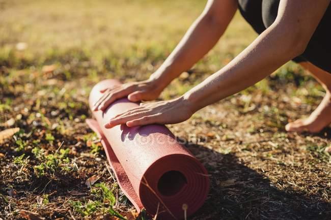Femme d'âge mûr dans le parc, le roulement des tapis d'yoga, gros plan — Photo de stock