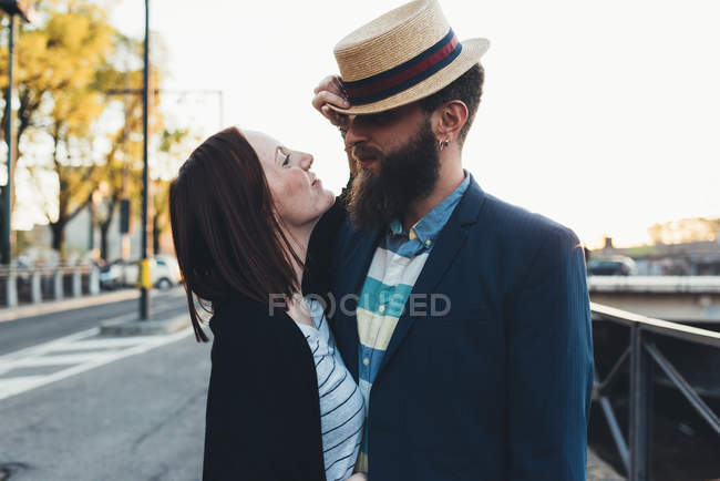Young woman pulling boyfriend's bowler hat by city canal — Stock Photo