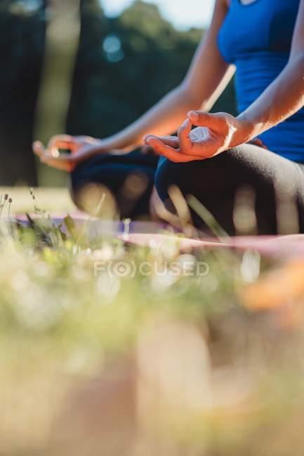 Donna matura nel parco, seduta in posizione yoga, vista angolo basso — Foto stock