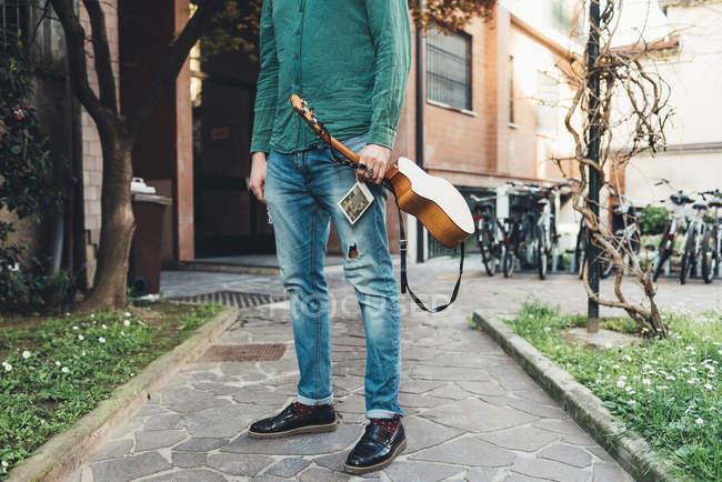 Cou bas vue curviligne homme debout tenant ukulele — Photo de stock