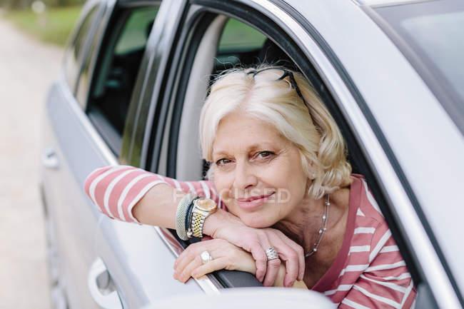 Портрет зріла жінка дивиться з вікна автомобіля на узбіччі дороги — стокове фото