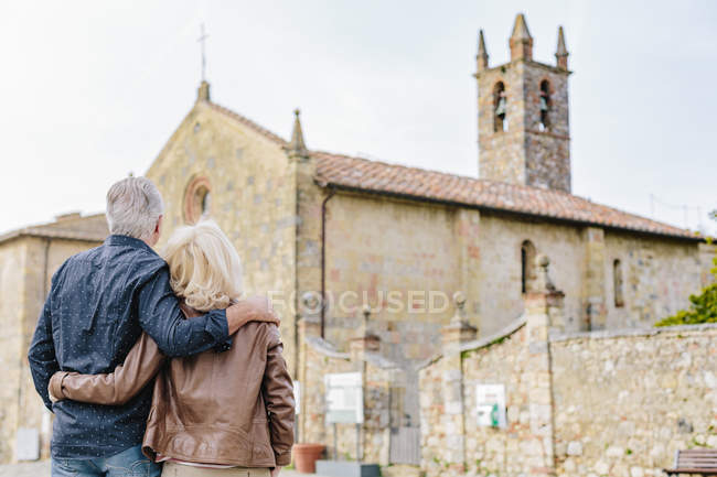 Rear view of tourist couple looking at church, Siena, Tuscany, Italy — Stock Photo