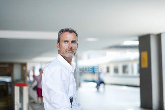 Mature businessman looking away from train station platform — Stock Photo