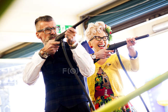 Quirky couple enjoying shooting gallery in amusement arcade, Bournemouth, England — Stock Photo