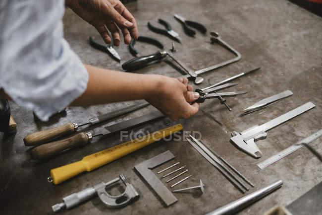 Mains du bijoutier femelle portant les outils à établi en atelier — Photo de stock