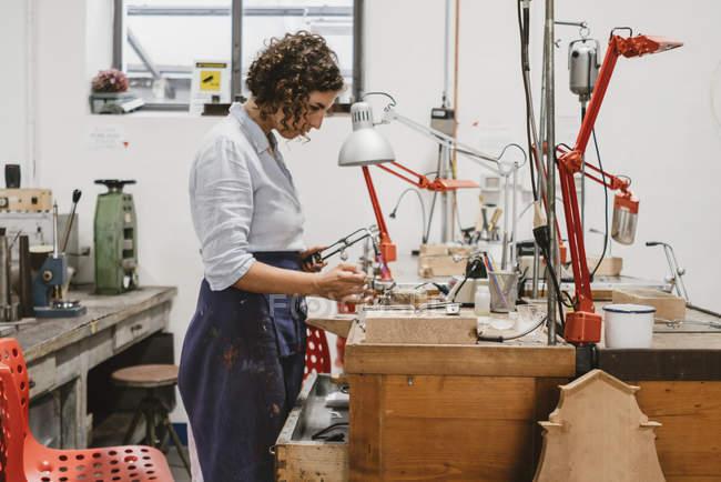 Bijoutier femelle à l'aide de lampe à souder au workbench — Photo de stock