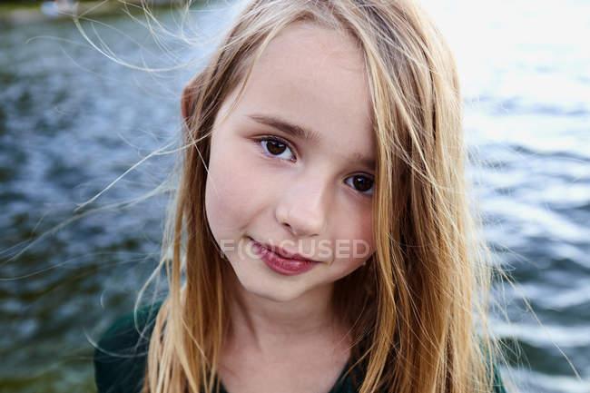 Девушка наслаждается рекой и смотрит в камеру — стоковое фото