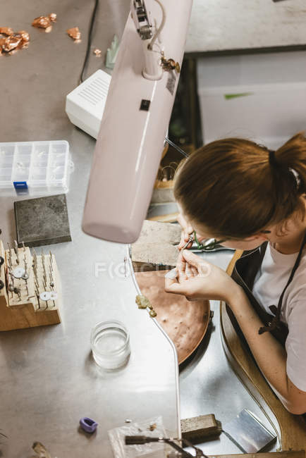 Overhead view of female jeweler using hand tool at workbench — Stock Photo