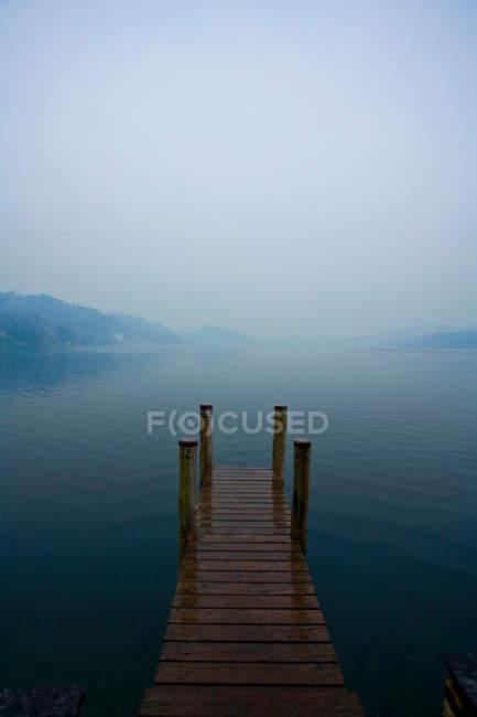 Пристань с гаванью и горами в тумане, Италия — стоковое фото