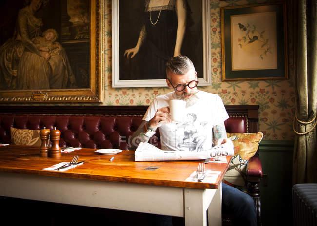 Вигадливий людина читання газет у барі-ресторані Борнмут, Англія — стокове фото