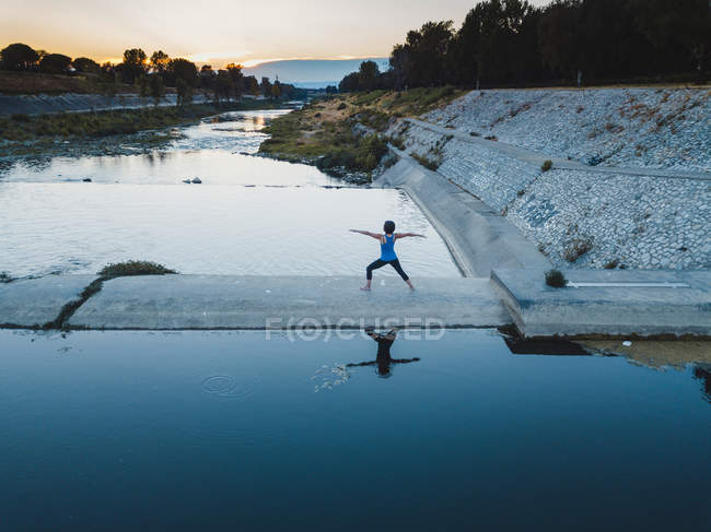 En plein air de femme d'âge mûr, à côté de l'eau, debout, bras tendus, en position d'yoga — Photo de stock
