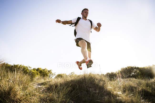 Молодой человек прыгает середине воздуха от песчаных дюн — стоковое фото