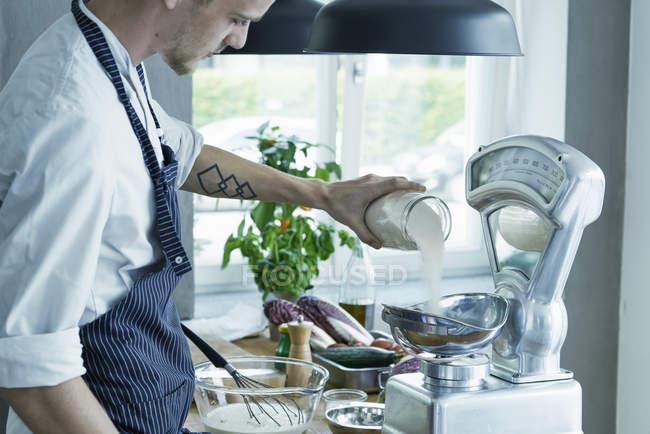 Cuoco unico maschio ingredienti di pesatura su vintage scale — Foto stock