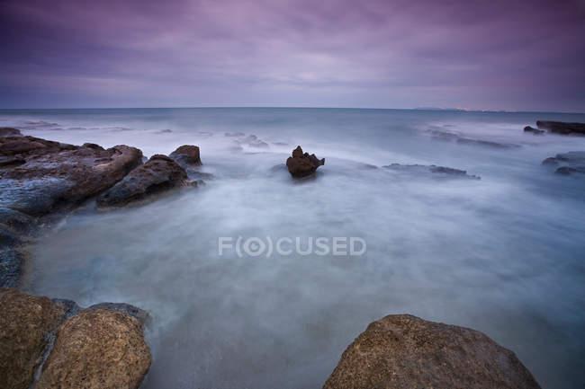 Time lapse vista delle onde sulla spiaggia rocciosa — Foto stock