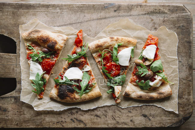 Pizza slices on chopping board, overhead view — Stock Photo