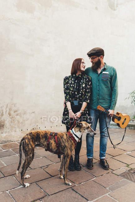 Cool couple with dog and ukulele on sidewalk — Stock Photo