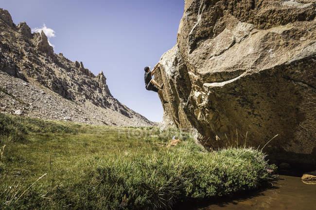 Boulderer masculino subiendo por la roca del valle, Parque Nacional Nahuel Huapi, Río Negro, Argentina - foto de stock