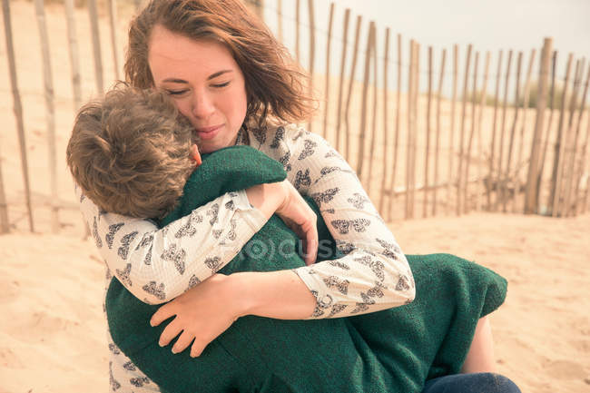 Young woman on beach hugging son — Stock Photo