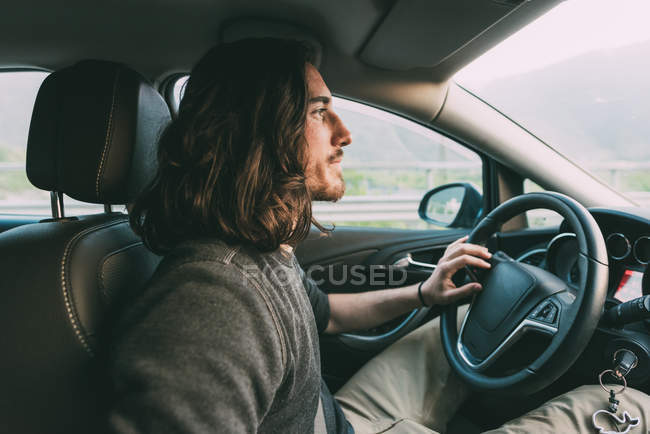 Молода людина, водіння автомобіля сільська дорога — стокове фото