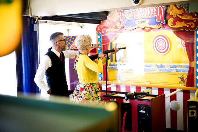 Skurrile paar genießt Schießbude in Spielhallen, Bournemouth, England — Stockfoto