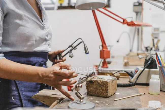 Mid section of female jeweler using blow torch at workbench — Stock Photo