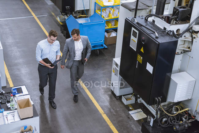Two male managers walking and talking in factory — Stock Photo