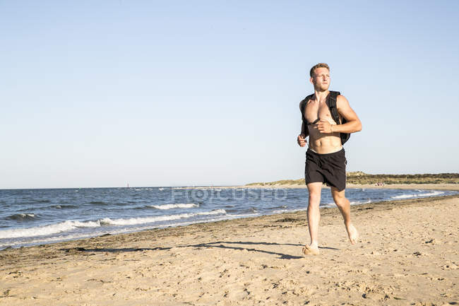Young male runner in shorts and backpack running along beach — Stock Photo