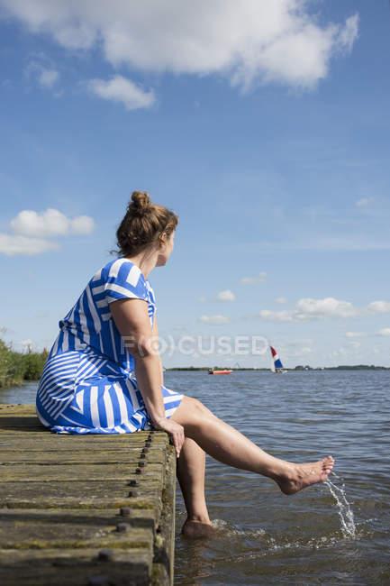 Женщина, сидящая на причал в районе озера фризских винтажное платье, снек, Фрисландии, Нидерланды — стоковое фото