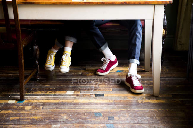 Jeans and trainers worn by couple sitting at table — Stock Photo