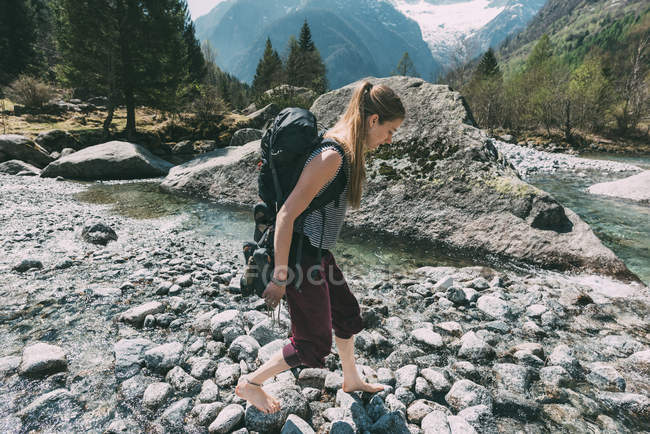 Barefoot woman stepping over river stones — Stock Photo