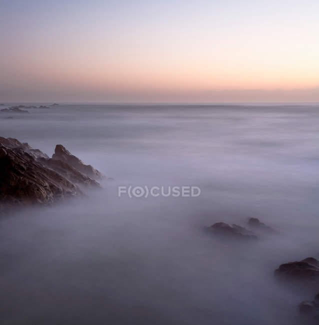 Aerial view of majestic rocky coastline in fog at sunset — Stock Photo