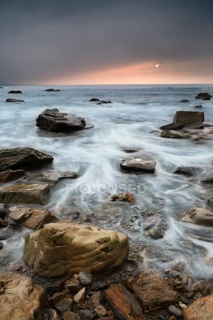 Вид волн на скалистом пляже с временной задержкой — стоковое фото