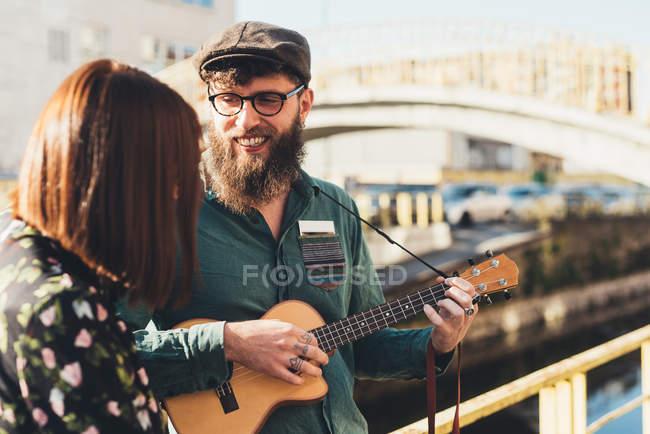 Hipster couple playing ukulele by canal — Stock Photo