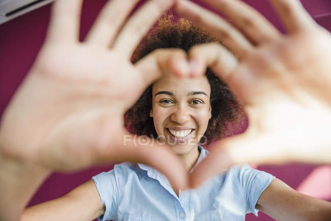 Portrait of young woman making heart shape with hands and fingers — Stock Photo