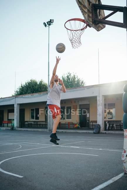 Мужчина прыгает на баскетбольное кольцо на детской площадке — стоковое фото