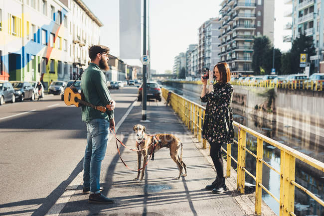Young woman photographing boyfriend and dog by canal using instant camera — Stock Photo