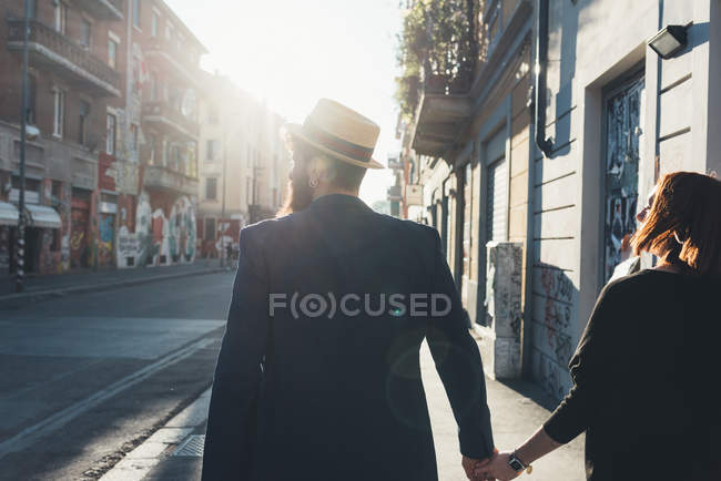 Rear view of cool couple strolling on sunlit street — Stock Photo
