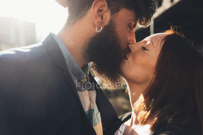 Casal legal beijando na rua iluminada pelo sol — Fotografia de Stock