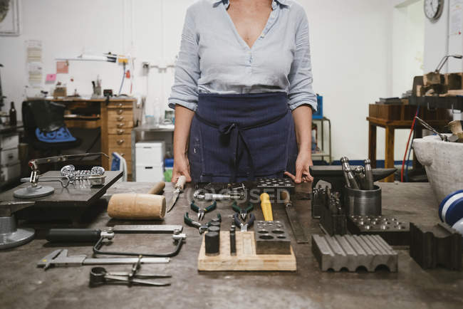 Mid section of female jeweller laying out hand tools at workbench in jewellery workshop — Stock Photo