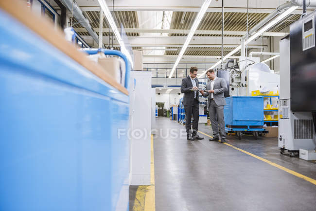 Factory managers inspecting product on factory production line — Stock Photo