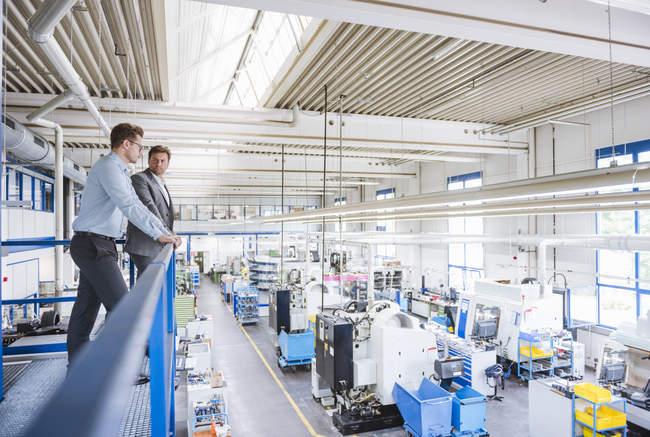 Zwei männliche Manager mit Blick vom Balkon der Fabrik am Fließband — Stockfoto