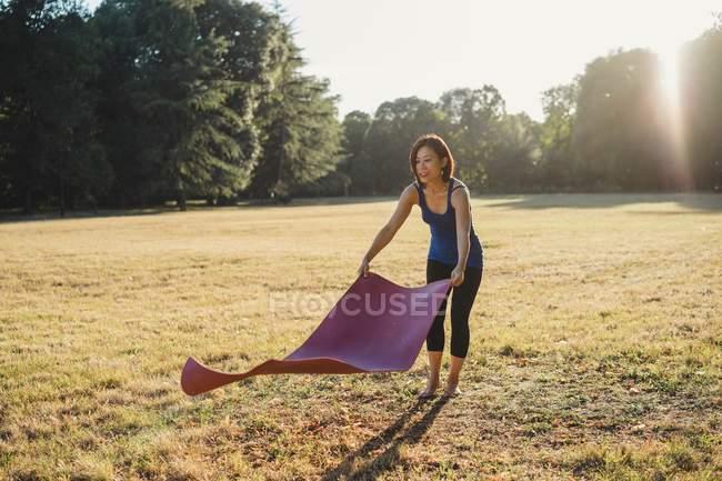 Femme d'âge mûr dans le parc, pose de tapis d'yoga sur l'herbe — Photo de stock