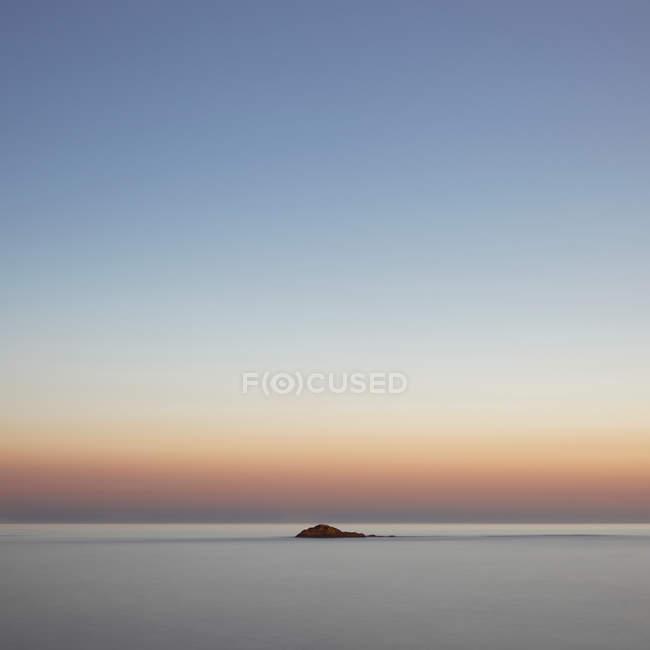 Bella vista panoramica di roccia in mare al tramonto — Foto stock