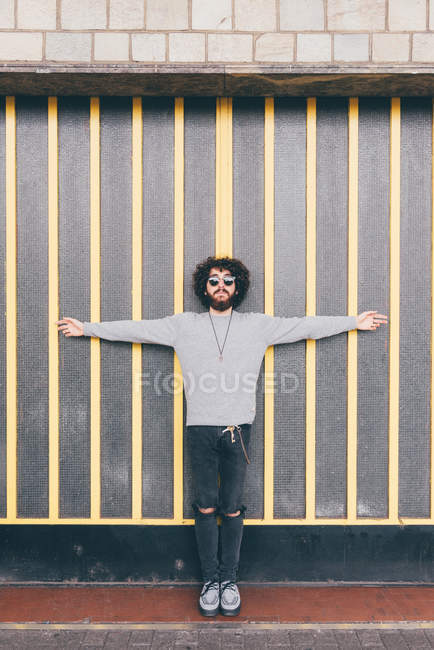 Portrait of young man, arms outstretched, in urban environment — Stock Photo