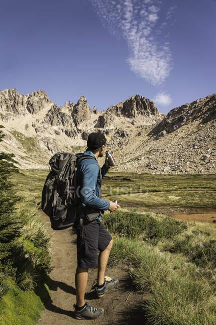 Senderista masculino tomando un descanso en valle montañoso, Parque Nacional Nahuel Huapi, Río Negro, Argentina - foto de stock