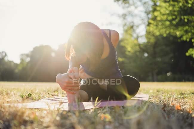 Зріла жінка в парку, сидячи, розтягування в позиції йоги — стокове фото