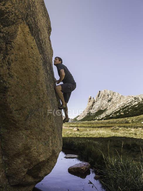 Male boulderer moving up valley boulder, Nahuel Huapi National Park, Rio Negro, Argentina — Stock Photo