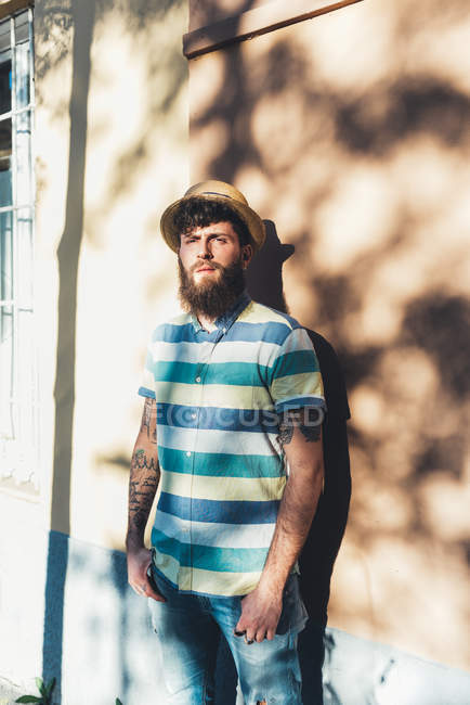 Portrait of man in straw boater leaning against sunlit wall — Stock Photo